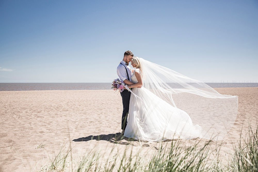 Bride and groom together on a beach while the veil blowns in the breeze | Image © https://melbrownweddings.co.uk/