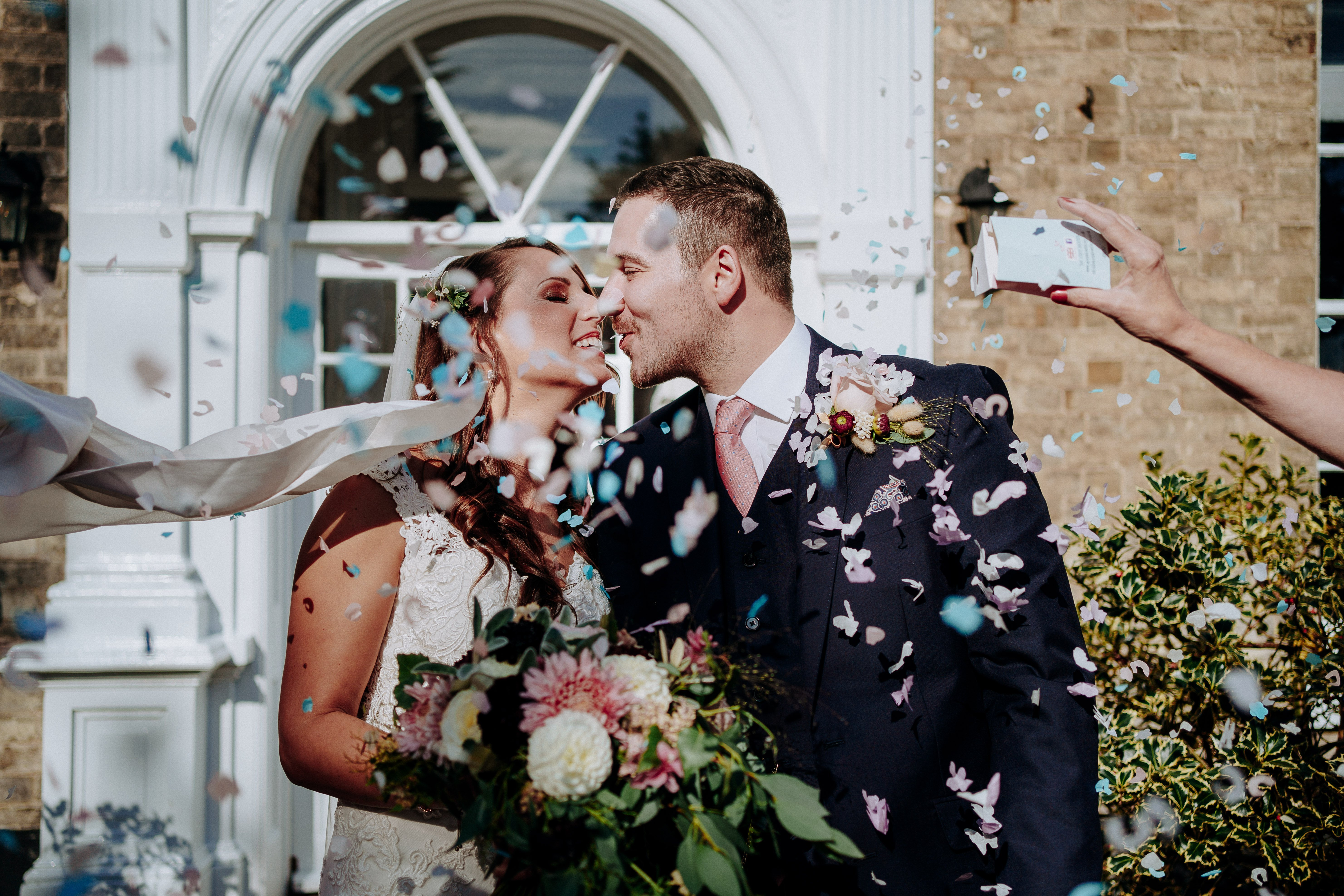 Bride and Groom kissing under confetti with bridal bouquet