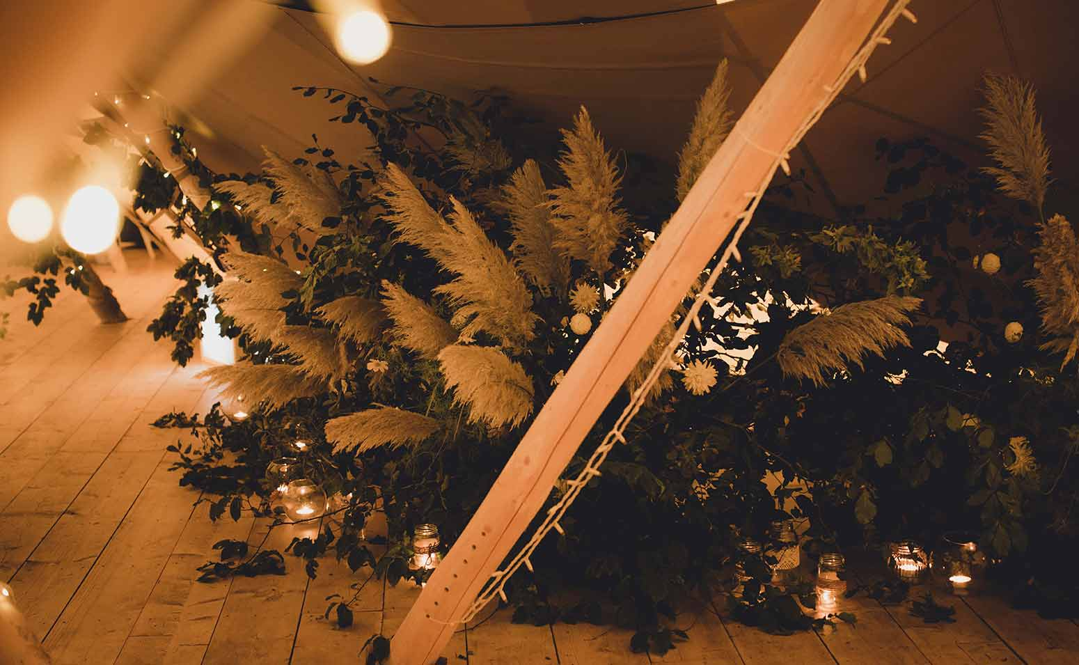 Floral installation of greenery and pampas in a tipi Image © SarahSalottiPhotography