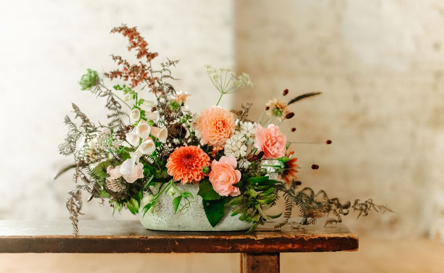 An arrangement of seasonal British flowers in shades of peach sat on a bench
