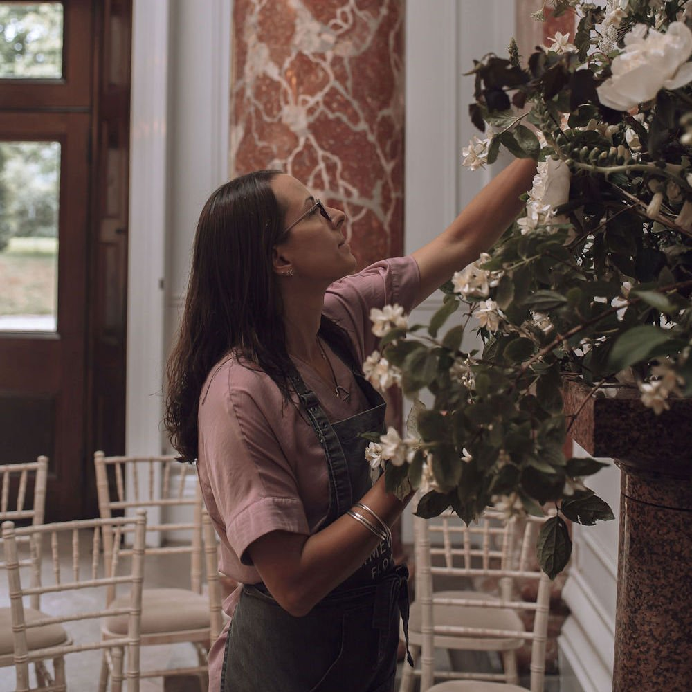 Fran the florist adding flowers to a large mantlepiece display